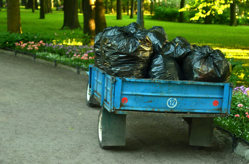 Trailer with many bags of plant garbage in the garden.Periodic garbage collection.
