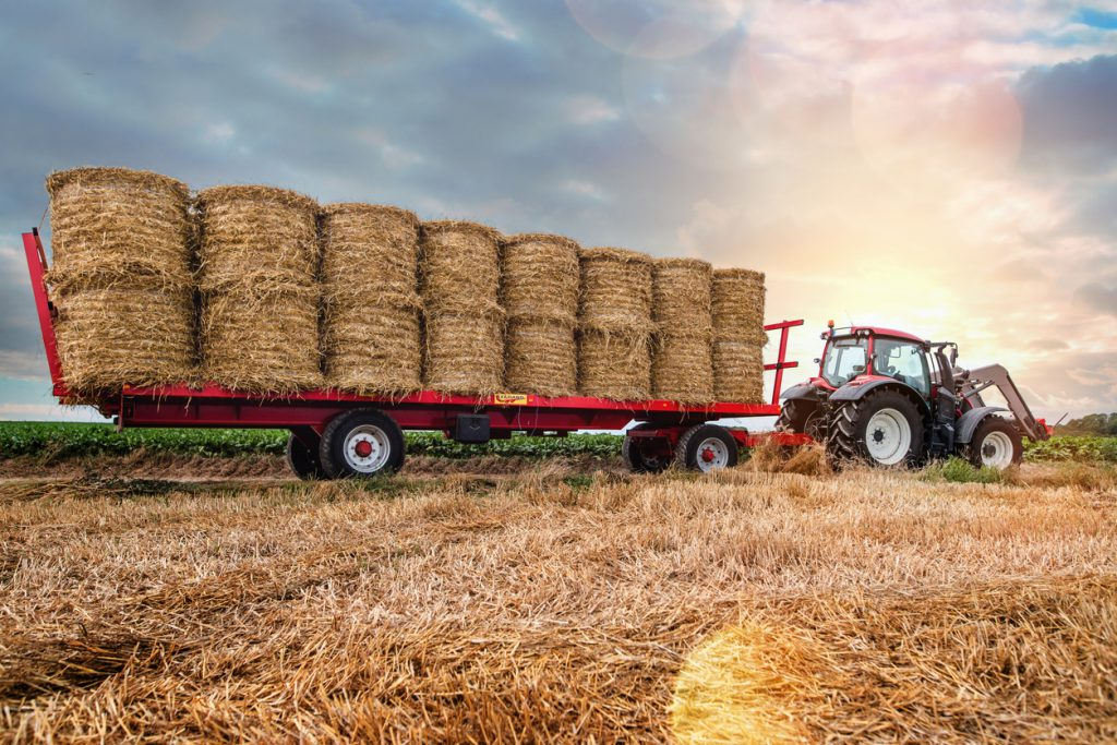 types of trailer hitches - agricultural hay trailer connected to a tractor in a field