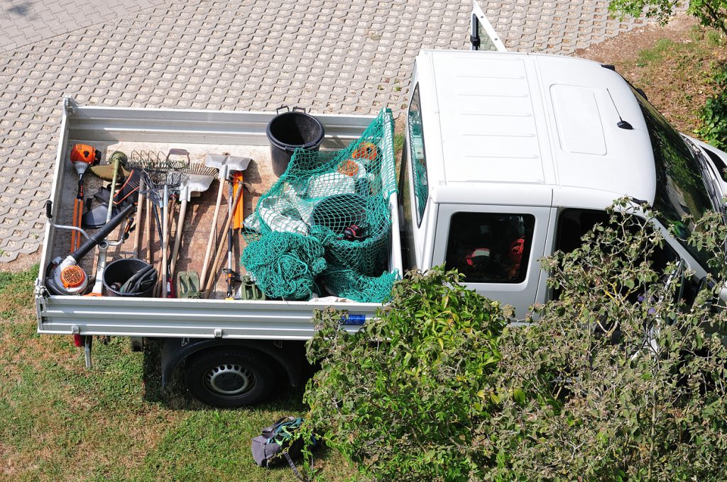 service body truck bed pickup of a gardening team with tools on loading area