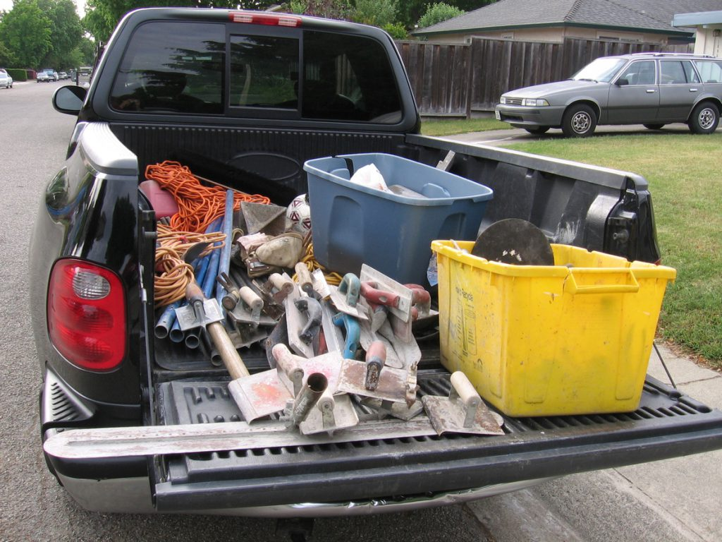Bed of a shiny black pickup truck containing tools for working with concrete