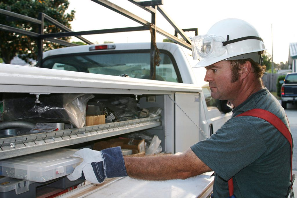 """""""An electrician reaching onto his service truck, in a suburban neighborhood. Model is a licensed Master Electrician."""""""