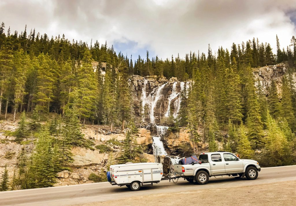 Columbia Icefield, Alberta, canada - June 2018: Truck pulling a camping trailer on a scenic road through the Columbia Icefield in Alberta, Canada.