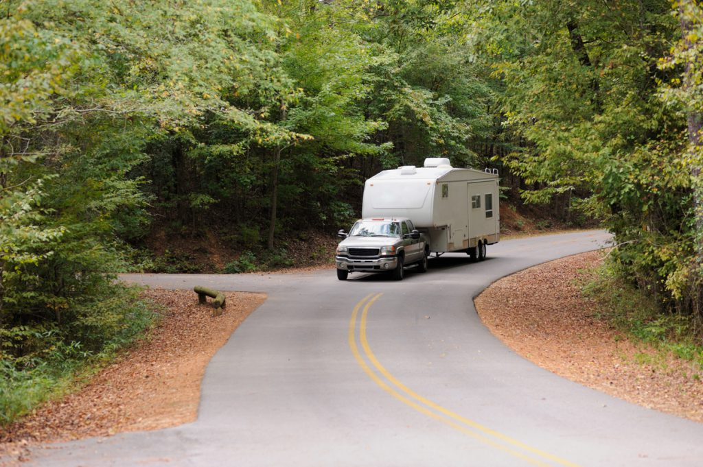Recreational vehicle fifth wheel travel trailer being towed down curving road in woods.